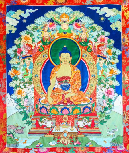 Elaborate Silk Appliqué Thangka of Buddha Shakyamuni surrounded by symbols of the Six Perfections. Original textile artwork completed in 1997. Materials: Silk satin & brocade, gold, pearls, horsehair. Dimensions: 78″ x 50″ (198 x 127 cm) including brocade frame. Traditional thangka format: rollable with veil and ribbons and ties at top for hanging.